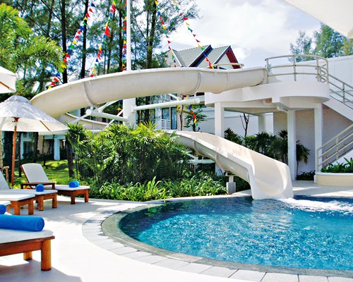 An outdoor swimming pool with water slide chaise lounge chairs and sunshades.