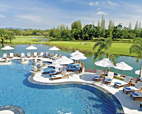 An outdoor pool with chaise lounge chairs and umbrellas alongside well maintained golf course with the waterfront.