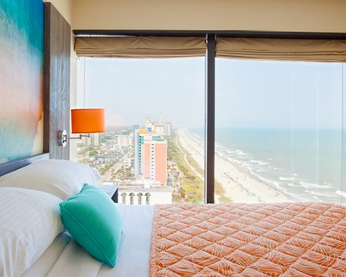 A well furnished bedroom with queen bed and ocean view.