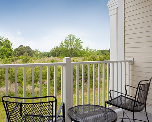 Balcony with patio furniture with view of wooded area.