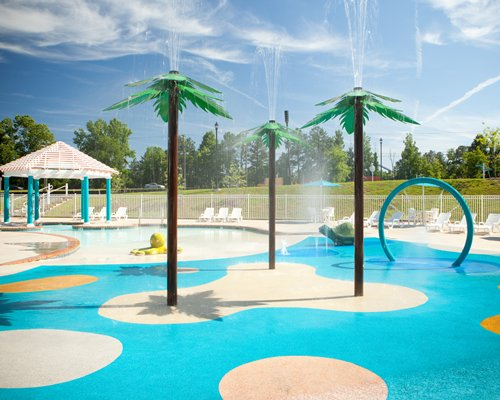 An outdoor swimming pool with water sprinklers and chaise lounge chairs.
