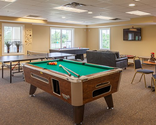 An indoor recreational area with a pool table and a ping pong table.