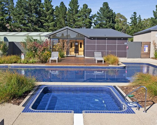 Outdoor swimming pool and hot tub with chaise lounge chairs and landscaping.