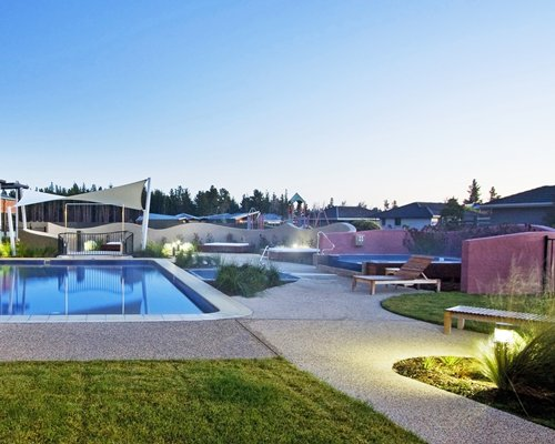 Outdoor swimming pool with a pathway chaise lounge chair and landscaping.