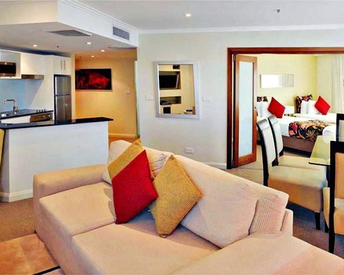 An open plan living room dining room and kitchen with an enclosed bedroom.