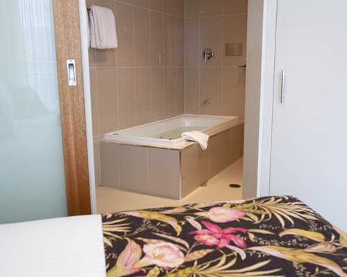 A well furnished bedroom alongside bathroom with a bathtub.