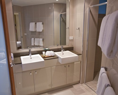 A bathroom with two sinks and vanity.