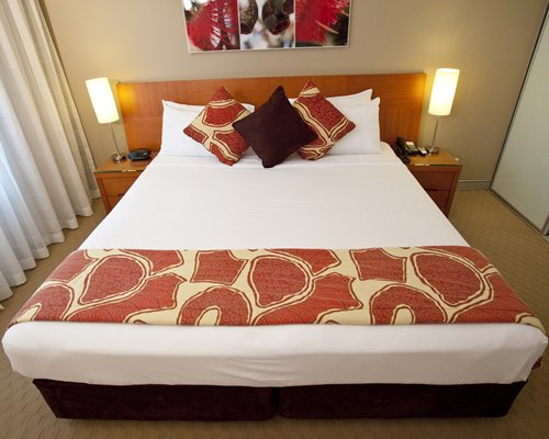 A well furnished bedroom with a queen size bed and an outside view.