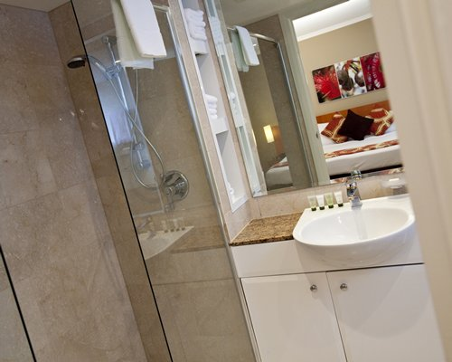 A bathroom with a sink vanity and a shower stall.