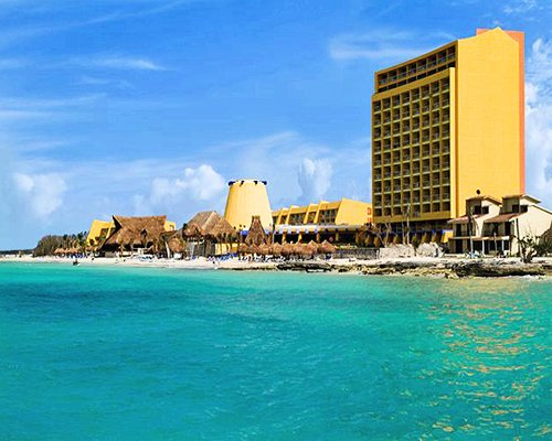 Exterior view of Club Melia At Melia Cozumel alongside the beach with thatched sunshades.