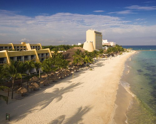 Exterior view of Club Melia At Melia Cozumel alongside the beach with thatched sunshades and palm trees.
