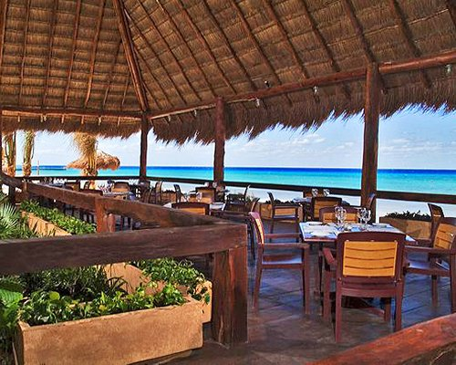 Thatched covered restaurant alongside the ocean.