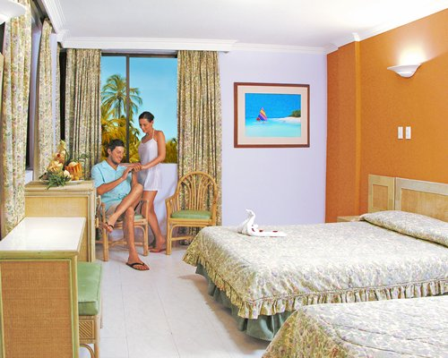 A couple in a well furnished bedroom with two twin beds and outside view.