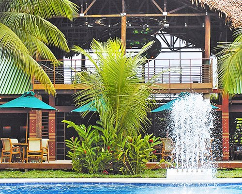 Outdoor swimming pool with fountain alongside a restaurant with sunshades and landscaping.