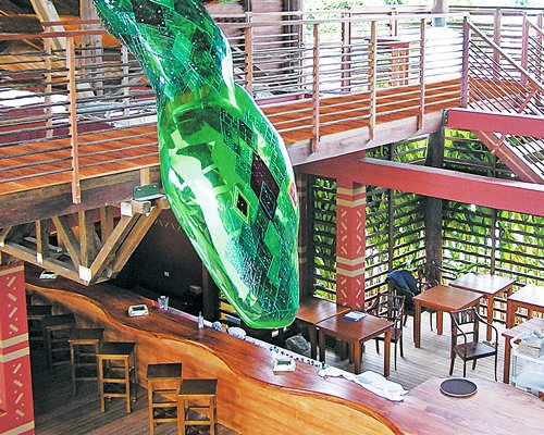 Restaurant with snack bar and stairway leading to an indoor balcony with an artificial snake.