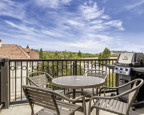 Balcony with patio furniture and barbecue grill.