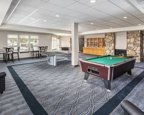 An indoor recreational room with pool table ping pong and fire in the fireplace.