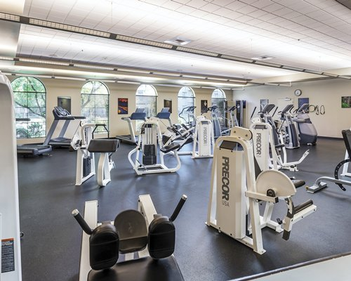 A well equipped fitness center with an outside view.