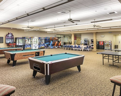 An indoor recreational room with pool tables arcade games and ping pong.