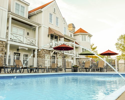 Outdoor swimming pool with a hot tub and chaise lounge chairs alongside the unit with multiple balconies.