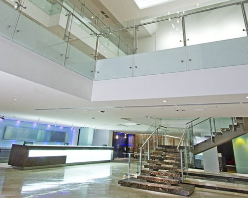 A well furnished large reception at the Hotel Four Points By Sheraton Cali with a stairway.