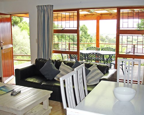 A well furnished living room with dining area balcony and patio furniture.