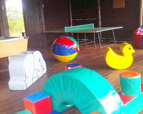 An indoor recreation area with pool ping pong table and kids playscape.