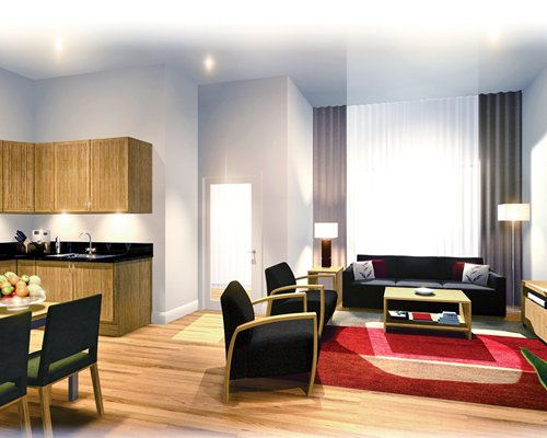 An open plan living room with a sofa dining and kitchen area.