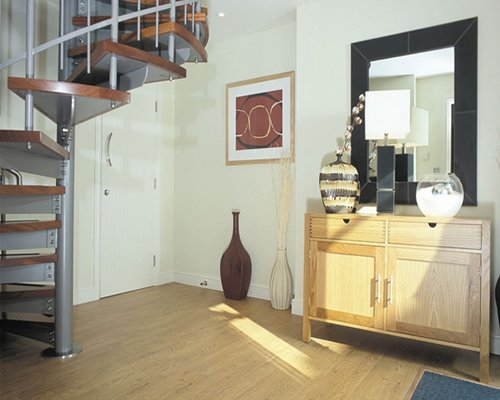 Living room with a vanity and spiral staircase.