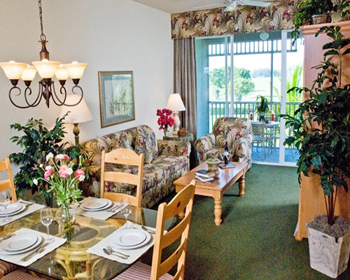 An open plan living and dining area with potted plants and a patio.