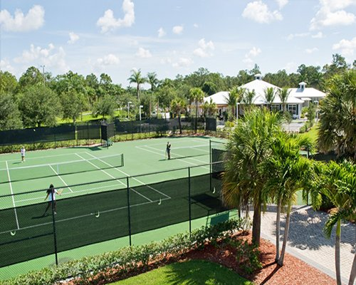An outdoor tennis court alongside multi story resort unit with trees.