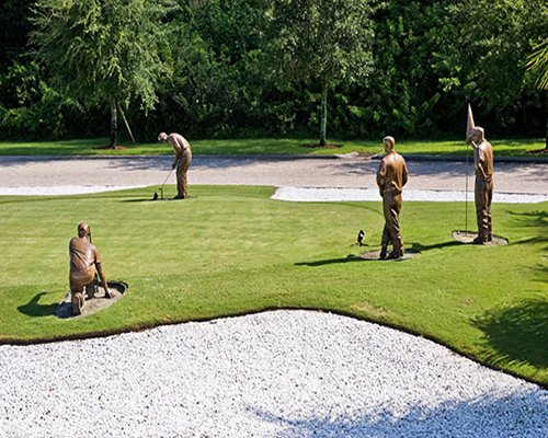 A well maintained lawn alongside statues.