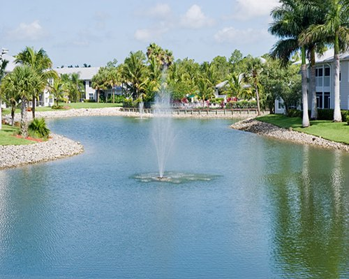 View of the waterfront with a sprinkler surrounded by trees alongside resort units.