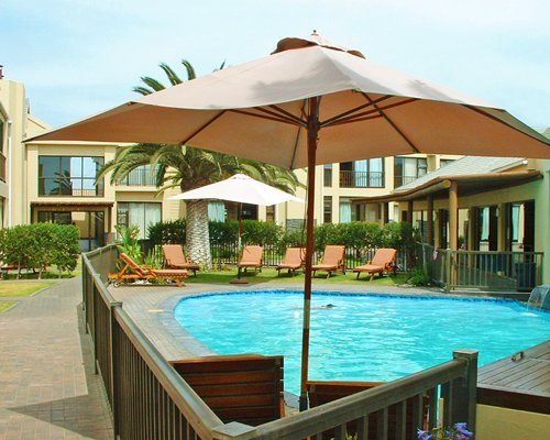 An outdoor pool with chaise lounge chairs and umbrellas alongside the resort.