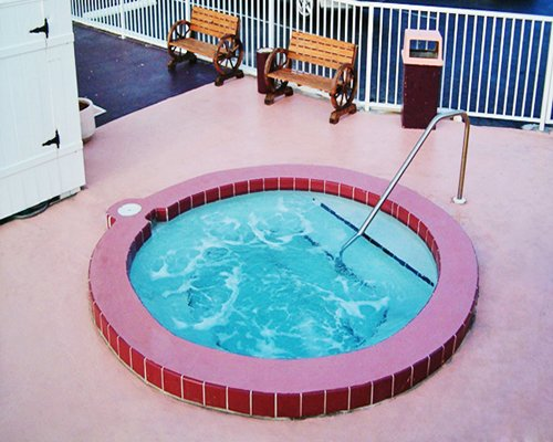 An outdoor hot tub with picnic chairs.