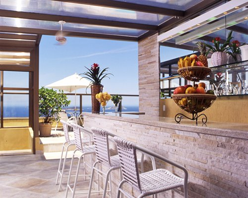 A well stocked indoor bar with a view of the ocean.