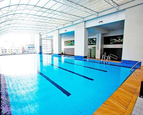 A large indoor swimming pool with an outside view.