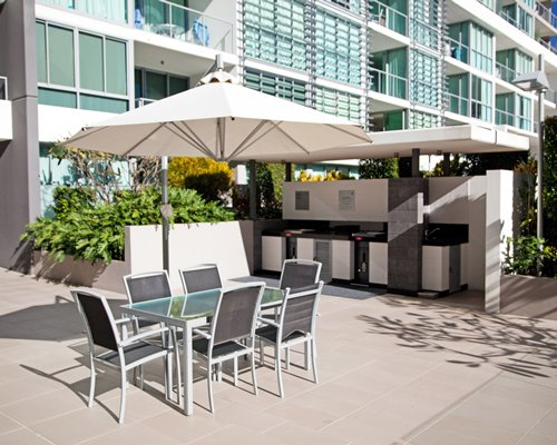 An outdoor dining area with shrubs alongside multi story resort units.