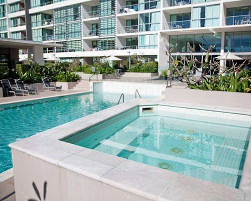 An outdoor swimming pool with a hot tub alongside resort units.