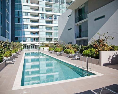 A scenic outdoor swimming pool with chaise lounge chairs alongside multi story units.