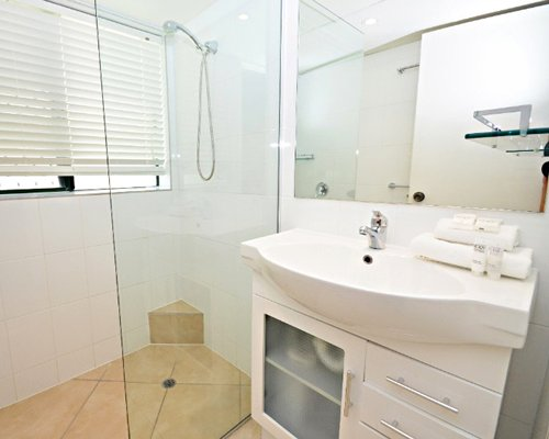 A bathroom with single sink vanity and stand up shower.