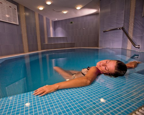 A woman relaxing in an indoor swimming pool.