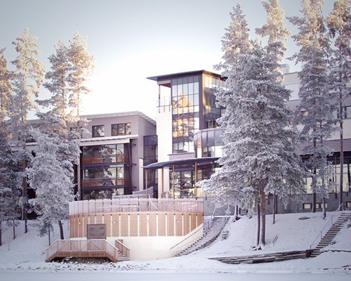 An exterior view of multi story resort units alongside trees covered in snow.