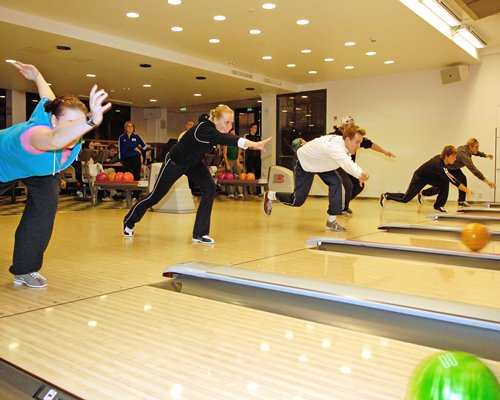 View of people playing in an indoor bowling alley.
