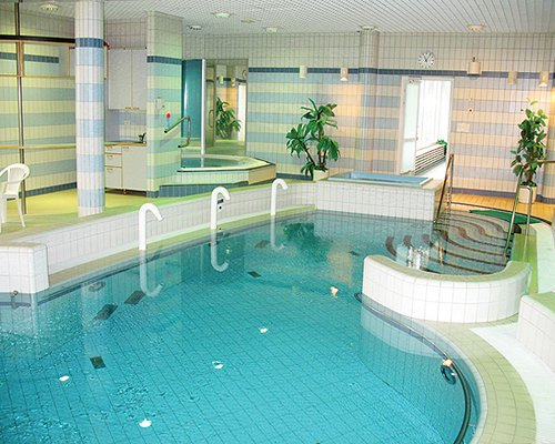 An indoor swimming pool with a hot tub.