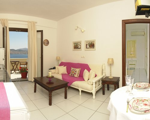 A well furnished living room with a dining table and outside view.