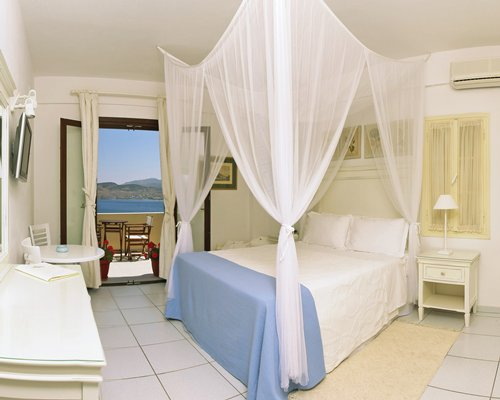 A well furnished bedroom with television and balcony with patio chairs.