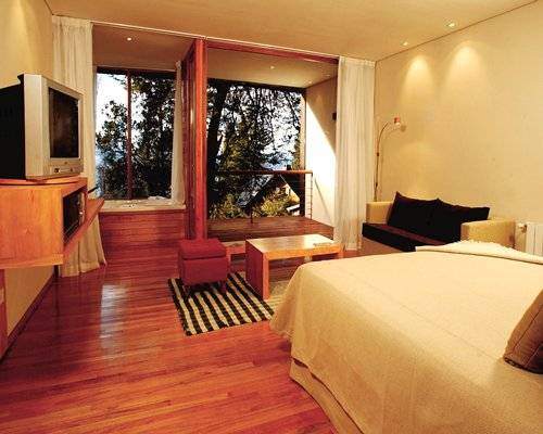 A well furnished bedroom with a television bathtub and a balcony.