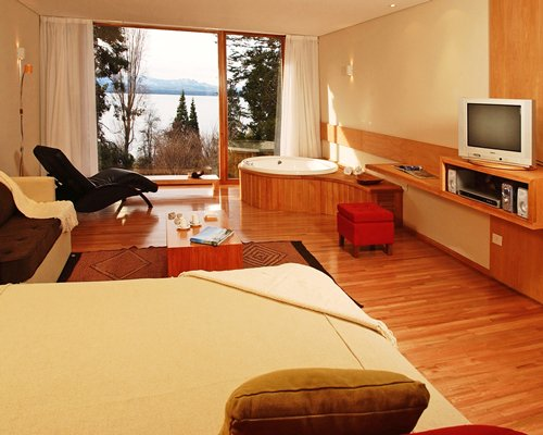 A well furnished bedroom with a television chaise lounge chair bathtub shower and outside view.