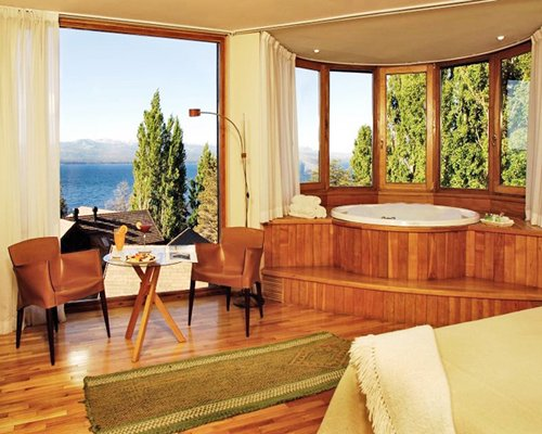 A well furnished bedroom with bathtub and an outside view.